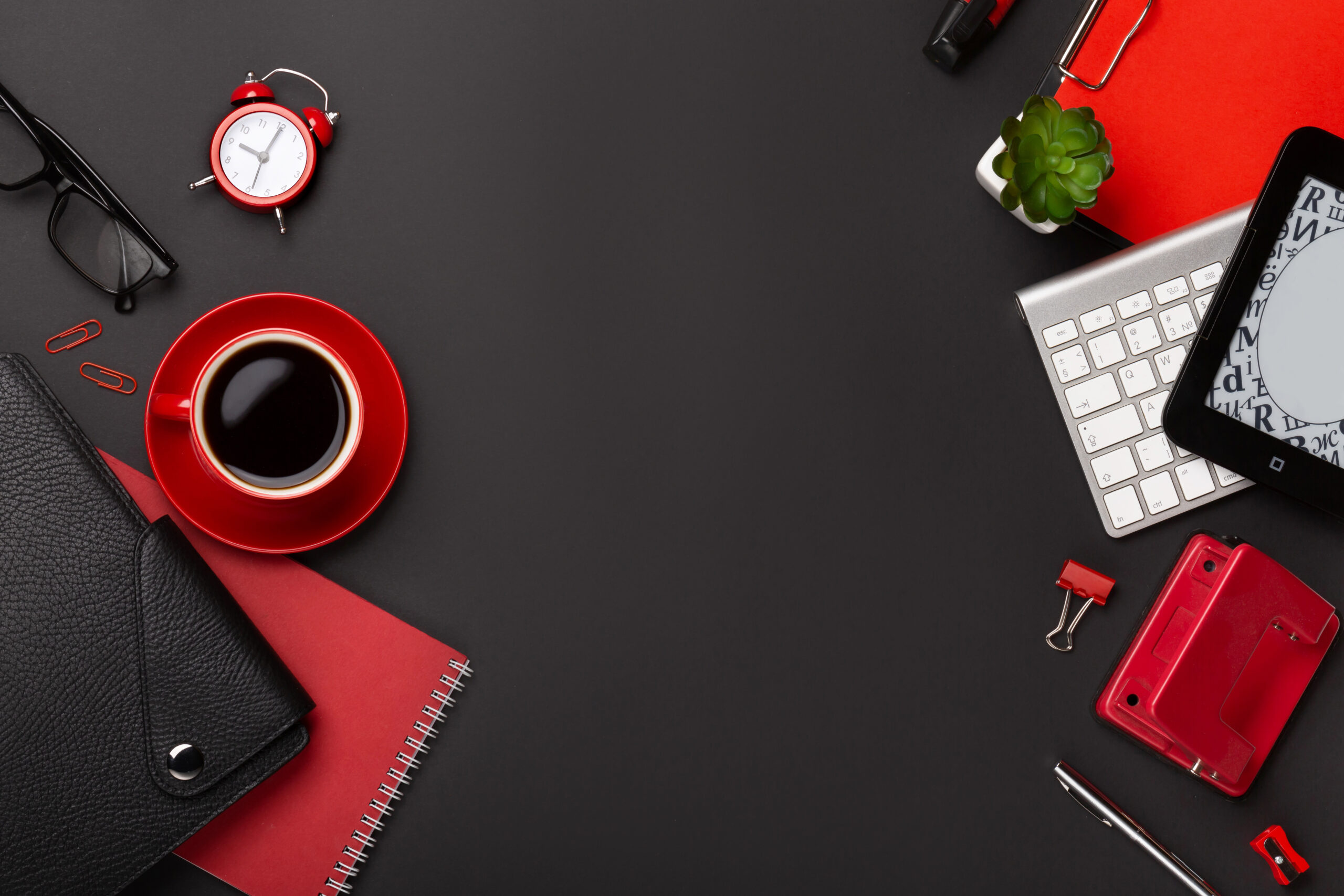 Black background red coffee cup notepad alarm clock flower diary scores keyboard on the table. Top view with copy space.
